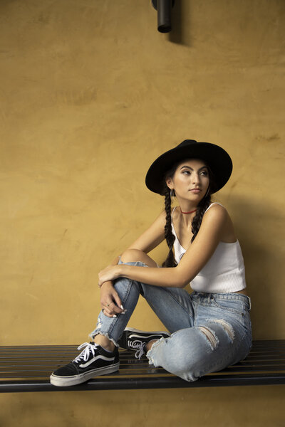 girl in a hat with a white tank and jeans on