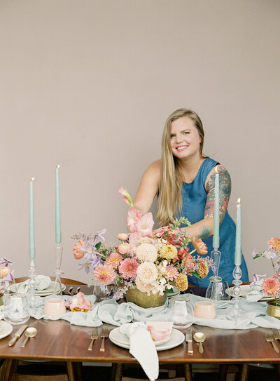 blonde-woman-wearing-blue-dress-at-a-table-with-colorful-flowers