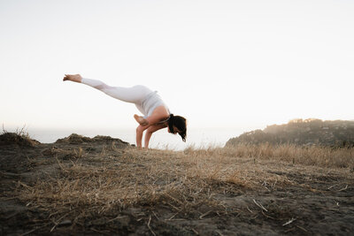 Erika Belanger in flying pigeon pose in a field