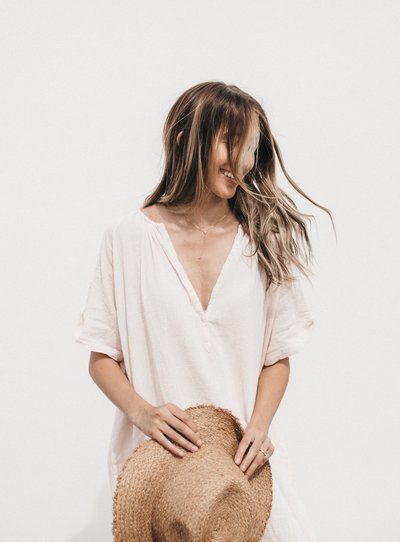 Model with long, ombre hair blowing in the wind. She's got beautiful bronze skin and is laughing while having her photo taken. Model is wearing a blush tunic and holding a straw hat by Made Well.