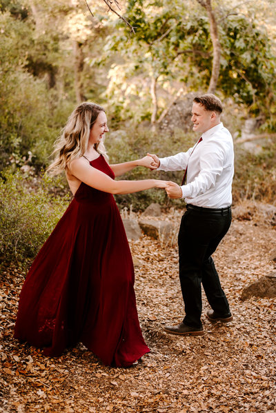 a couple dancing in a forest for their engagement