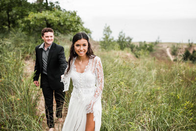 A bride and groom walk towards the camera through a field of long dune grass. The bride leading the groom by the hand and wears a long sleeve  white dress with lace top and chiffon skirt.
