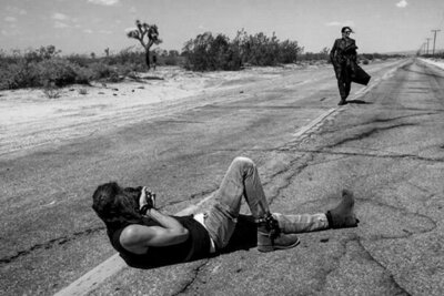 On Location Behind the Scenes Photo Mark MAryanovich lying on road in desert photographing Leslie Cours Mather