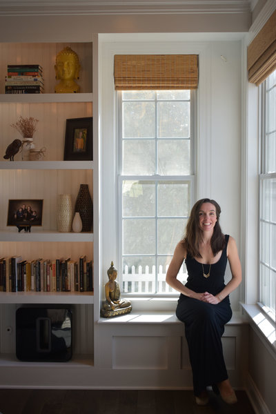 Christine Camarda seated in front of window with buddha, books, vases, photographs and other decor items as inspiration