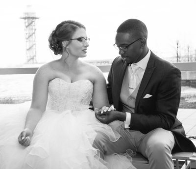 Groom holds bride's hand as they sit together in the Sheraton Erie Bayfront Hotel