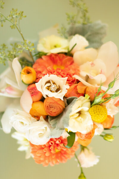 beautiful wedding ring nestled in yellow and orange wedding bouquet
