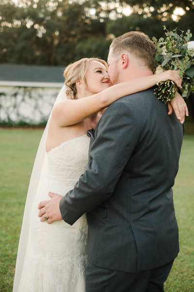 Bride with arms around groom's neck while holding her bouquet and  groom holding her waist while they kiss on their wedding day