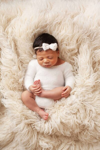 dark skin newborn girl white outfit bow fur rug