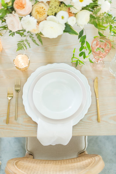 White, peach, and gold place setting on farm table