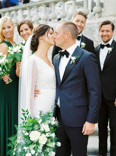 Jennifer and Alex Noren kissing on their wedding day in front of their wedding party