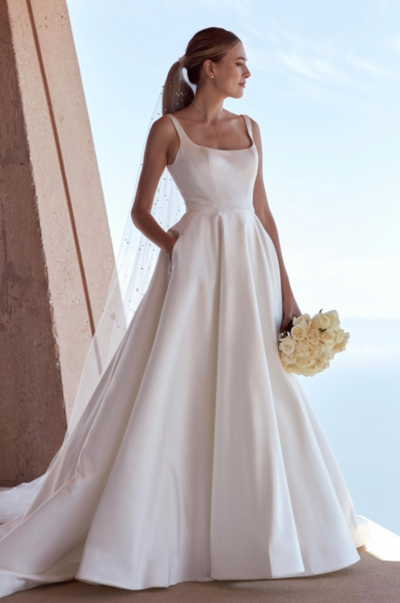 We crafted our jewel satin Kitt with a chapel train, a pair of (very necessary) pockets, and a modern square neckline for brides who are wanting something classic with a contemporary twist.