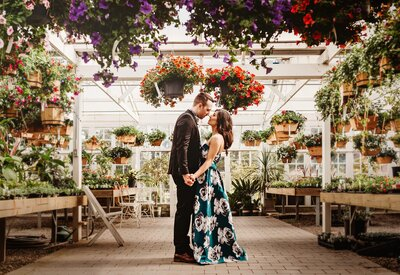 Couple embraces for engagement photograph in a greenhouse filled with light
