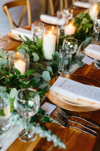 Dark hardwood farm tables dressed with a full strand of luscious greenery.  Shimmering gold chargers reflect the romantic light from tall pillar candles.