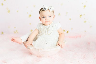 baby girl sitting in portrait studio with bow
