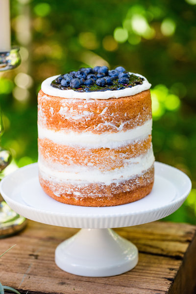 A delicious bare cake with blueberries on top