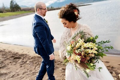 a bride in a shaggy sweater with a presentation bouquet walks along columbia river