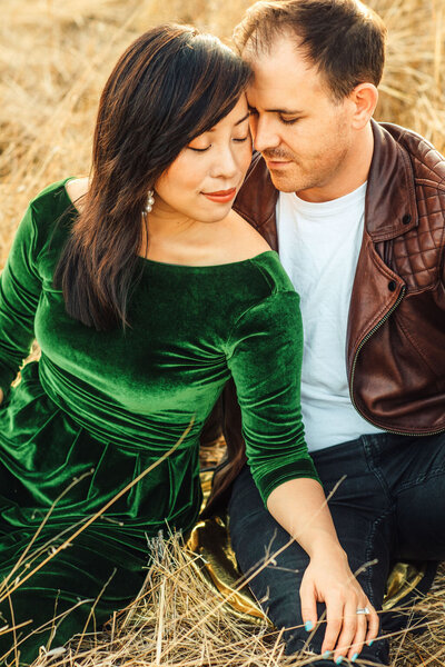 Couple embracing during photoshoot in open bright and airy field