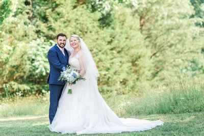 Bride and groom in green field blue white and blush flowers