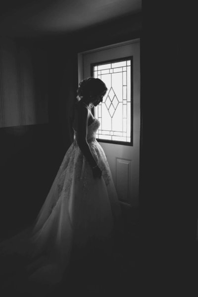 Bride standing a front door in wedding dress