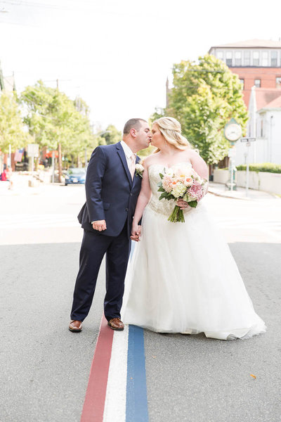 Bride & Groom kiss in the middle of the red, white & blue street in Bristol, RI