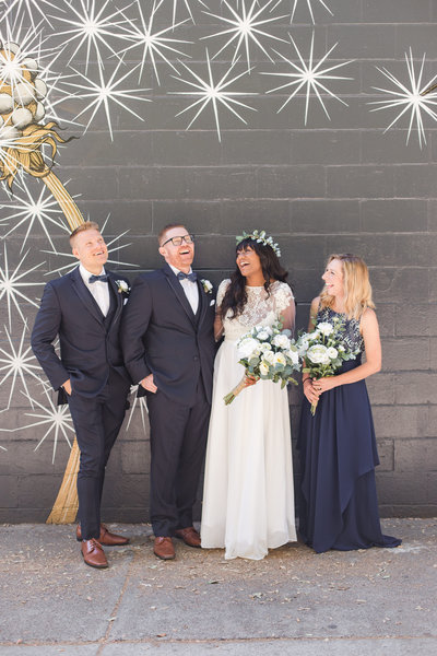 A bridal party laughs and celebrates in front of a mural at a Downtown Sacramento wedding.