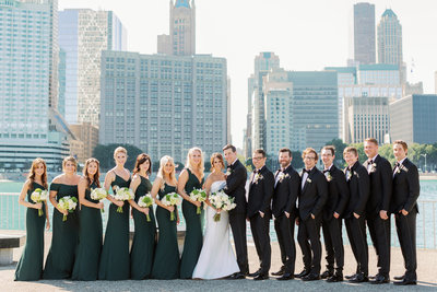 wedding party standing in front of a city seen