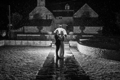 Bride and Groom laughing and standing in the rain