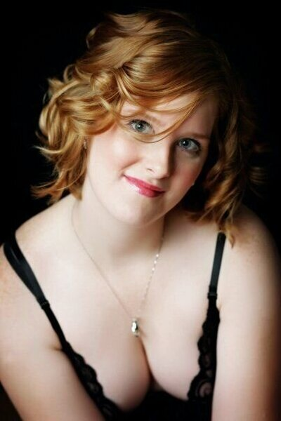 Red haired woman on a black background posing for a boudoir photo at Boudoir & Pinup By Janet Lynn Photography