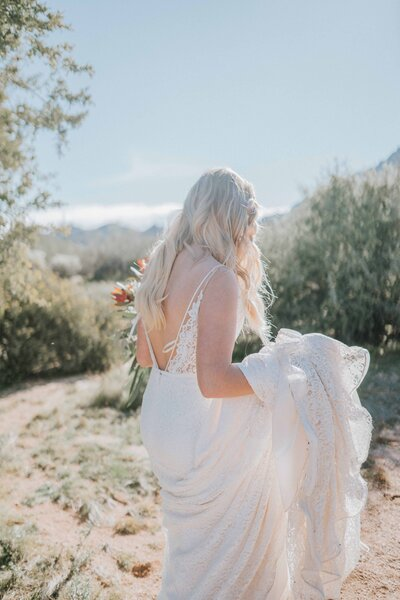 boho bride holding skirt of wedding dress walking through the desert after southern wedding in knoxville tennessee summer wedding