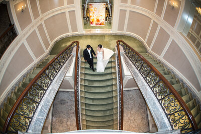 Bride and groom are walking down on a elegant indoor stairs.