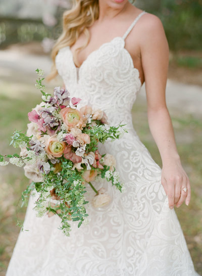 Bride in wedding dress outdoors holding wildflower bouquet