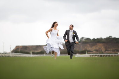 Bride and Groom running on racetrack at Del Mar Racetrack