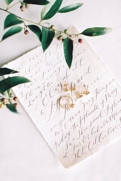 Light and Airy wedding detail photo showing gold jewelry on an invitation