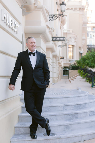 man wearing a black suit in front of hublot store in Monaco