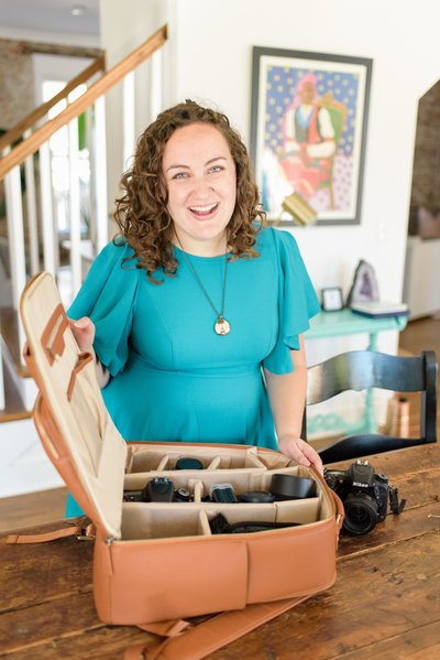 Nashville brand photographer packing her Kamrette camera bag in a teal dress