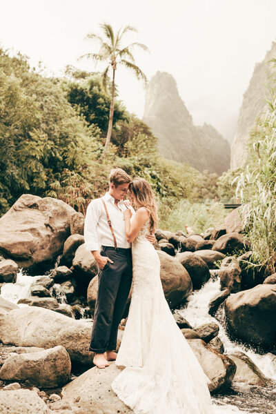 husband and wife standing near waterfall in hawaii