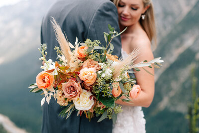 Bride holding colorful fall bouquet by Twisted Willow Floral at Washington Pass Overlook