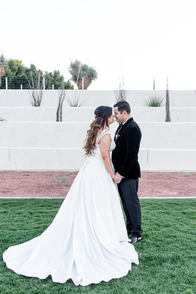 bride and groom hold hands and touch foreheads in scottsdale park