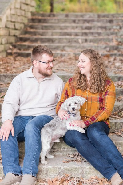 Engaged couple posing with their doggy.
