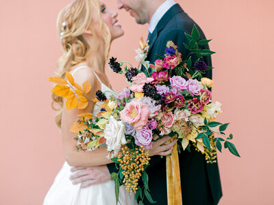 bride and groom smiling with colorful bouquet