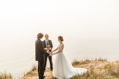 couple getting married on top of cliff overlooking water