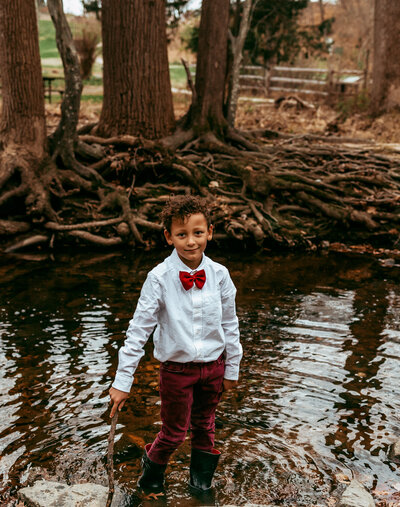 little boy plays in creek in a red bowtie.