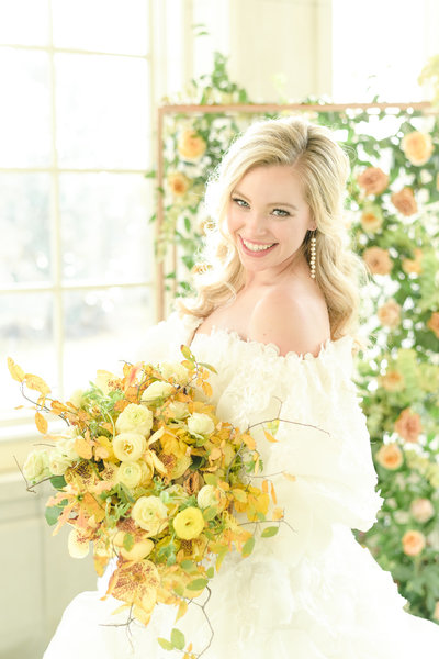 Blonde bride holds yellow bouquet and smiles