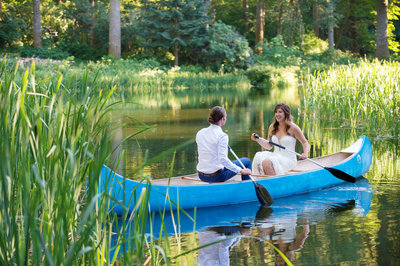 a bride and groom row in a bright blue boat at bridal veil lakes