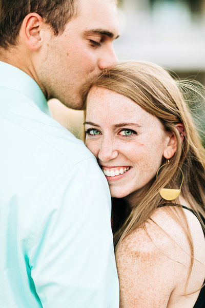 man kisses his fiance on the top of her head