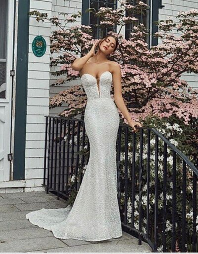 Beaded lace Sheath silhouette Romantic sweetheart neckline Detachable overskirt Extra bodice construction Cascading train