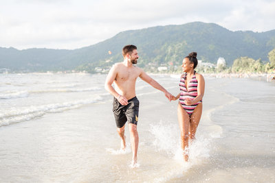 Couple engagement shoot on beach running through water