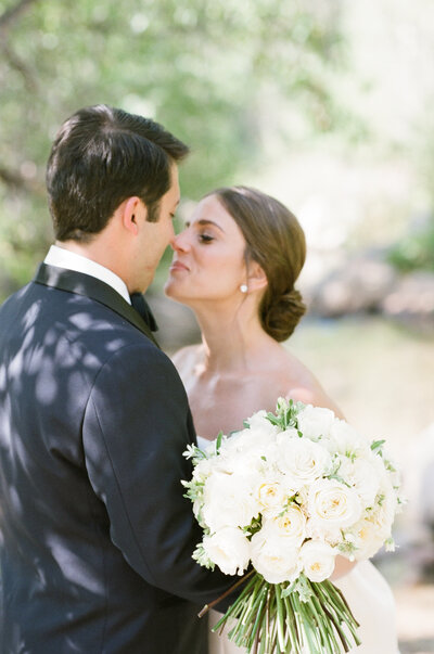 Bride leans in to kiss her groom, she holds a large white bouquet