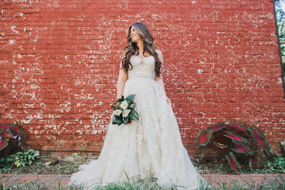 bride in front of a red brick wall