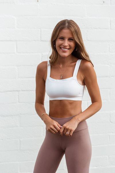 Fitness coach Lindsay Marcella standing in front of a white wall